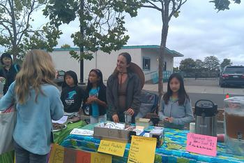 Miss Sarah at the Farmers Market with her student helpers.