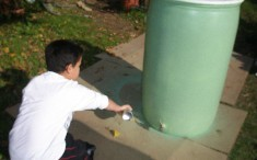 Spray painting the base coat for our rain barrels